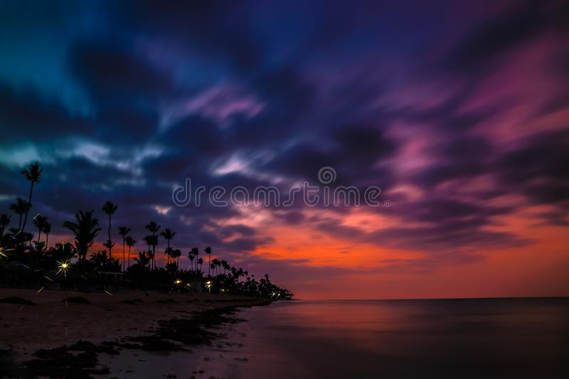 Dramatic sunset over the exotic beach, with palms royalty free stock image