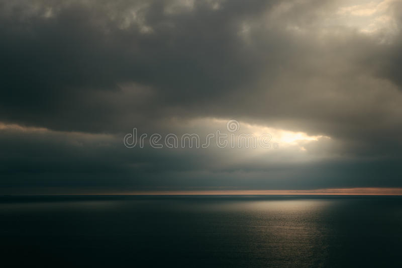 Dramatic sunset over green sea. Dark cloudscape stock photography