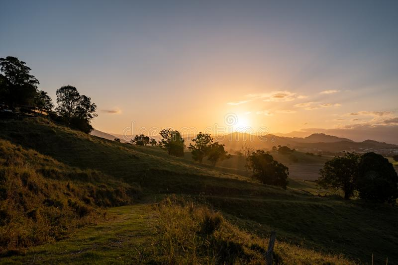 Dramatic sunset over Murwillumbah. As the sun sets it casts beautiful colours and shadows across the farm fields and landscape of Murwillumbah, NSW, Australia stock images