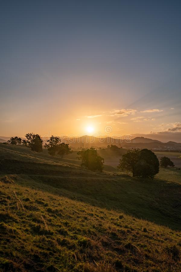 Dramatic sunset over Murwillumbah. As the sun sets it casts beautiful colours and shadows across the farm fields and landscape of Murwillumbah, NSW, Australia stock photos