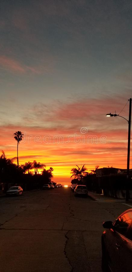 Dramatic Sunset over Pacific Ocean - Street view with Palms royalty free stock image
