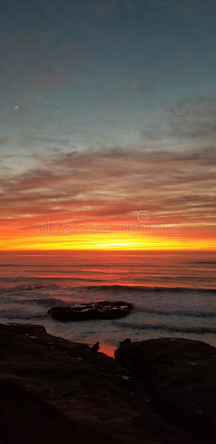 Dramatic Sunset over Pacific Ocean - Waves Crashing on the Rocks royalty free stock images