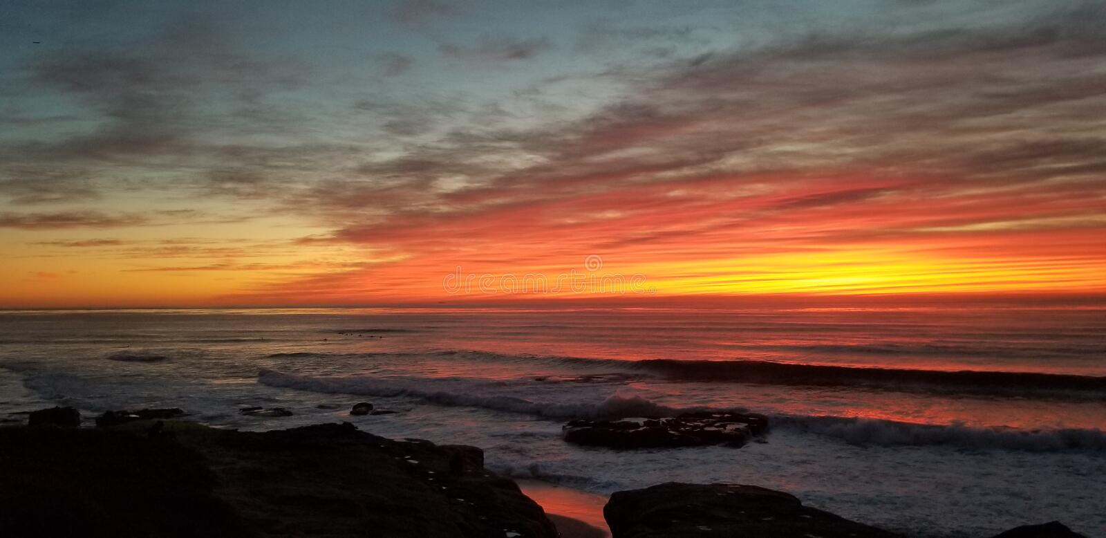 Dramatic Sunset over Pacific Ocean - Waves Crashing on the Rocks stock images