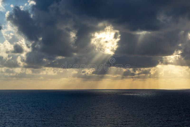 Dramatic sunset over sea water with gray clouds and sun lights royalty free stock photo