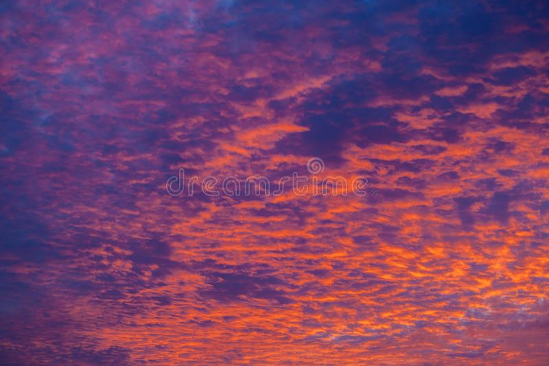 Dramatic sunset sky with clouds painted in vivid red and orange tones royalty free stock image