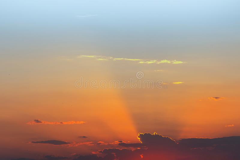 Dramatic sunset sky. Fiery bright colors of sun going down. Sunlight rays shining from behind clouds. Scenic nature background.  stock images