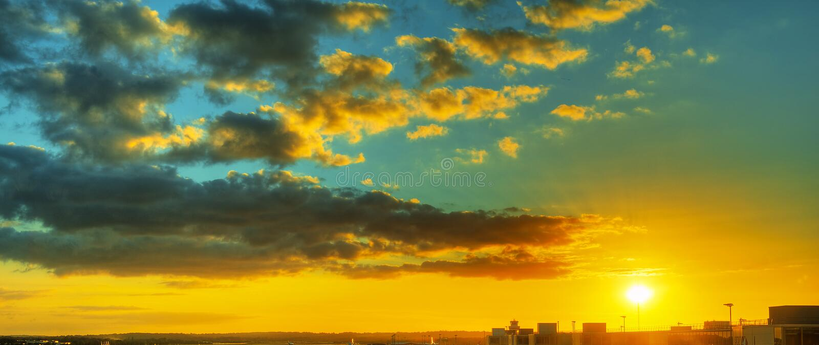 Dramatic sunset sky over industrial buildings stock image