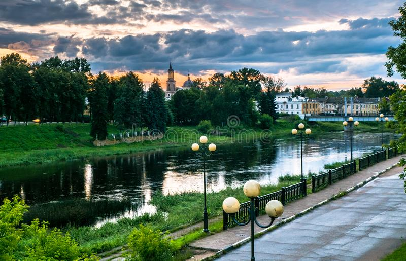 Dramatic sunset sky over the Tvertsa River and its picturesque shores after storm. Russian provincial town Torzhok, Tver region. Admirable view of the evening stock photo