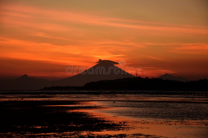 Sunset with smokey mount Agung volcano silhouette on Bali royalty free stock photos