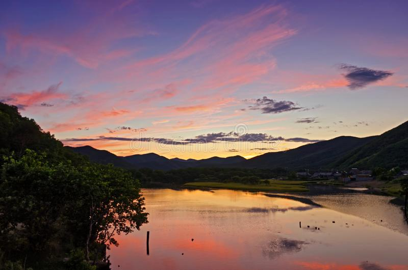 Dramatic sunset and sunrise sky with beautiful pink, yellow and blue clouds over the river and mountains royalty free stock images