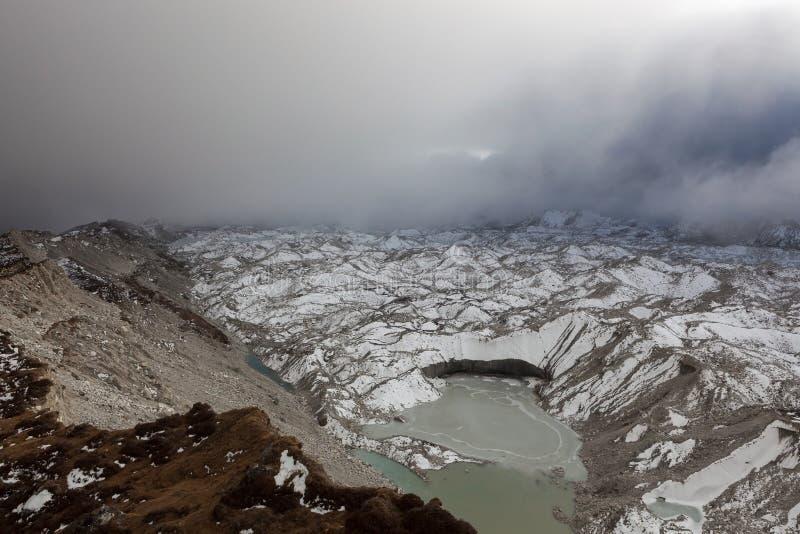 Dramatic view over Ngozumpa glacier and grey. Dramatic view over Ngozumpa glacier and grey moraine lake in Sagarmatha National Park, Himalayas, Nepal. Dark and stock image
