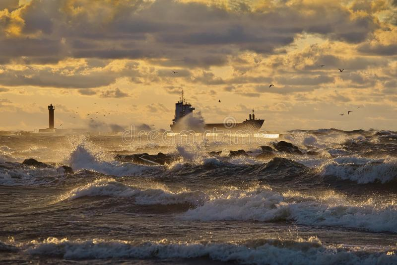 Vessel leaving a harbor and passing lighthouse and pier, breaking through stormy waves, lit by the yellow sunset light. Dramatic view to vessel leaving a harbor stock images