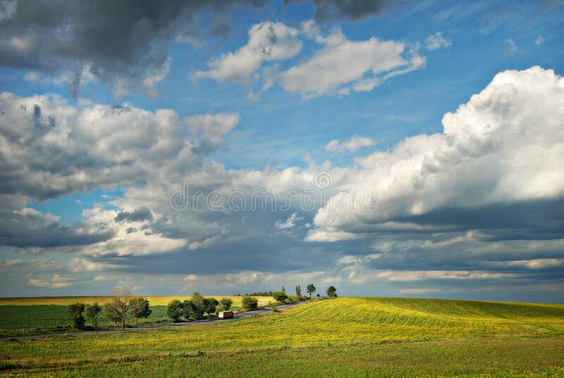 Truck On A Lonely Road Delivering. Dramatic view of a truck on a lonley road in spring, beautiful light, scenery and clouds, delivering goods for those in need royalty free stock images