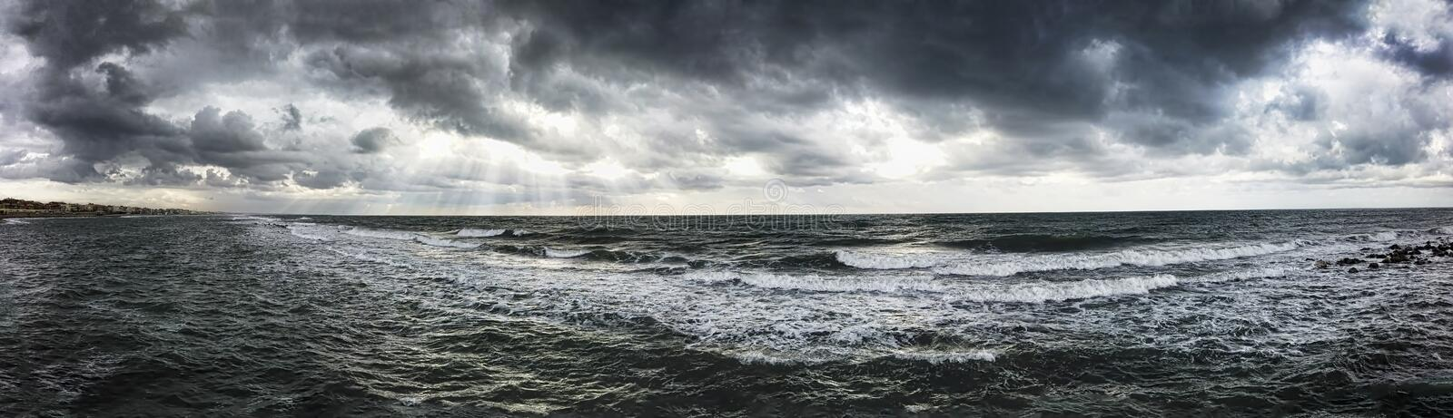 Dramatic weather panorama over the sea threatening waves crashing at the shore with overcast sky and sunbeams on the water royalty free stock images