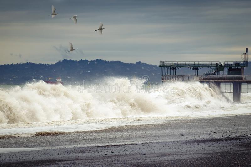 Dramatic weather - a storm on the sea, waves break about the pier, birds fly in sky. stock photos