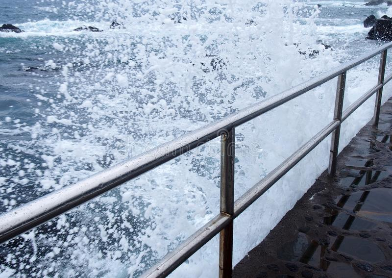 Dramatic white high foaming waves crashing over steel railings on a jetty a the edge of a summer blue sea stock images