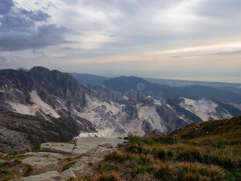 Dramatic wide angle view over the white marble quarries seen from Campo Cecina, Massa Carrara, Italy. Autumn, fall. Wide angle view over the white marble royalty free stock images