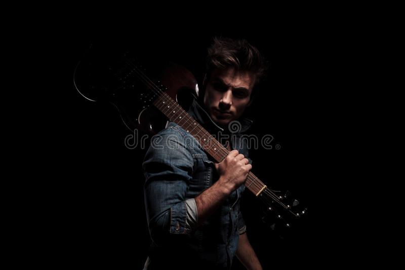 Dramatic young guitarist looking back while holding guitar on sh. Oulder, on black studio background stock images
