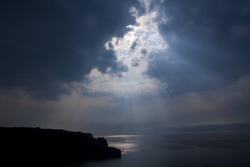 Dramatisch landschap van de kust in de schemering - de stralen van de zon maken hun manier door de wolken stock foto