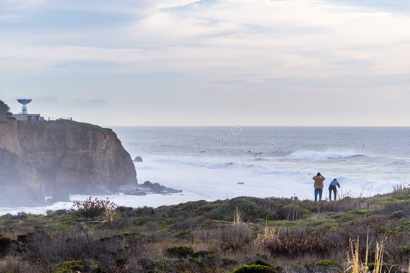 Dramatisch landschap van de Vreedzame Oceaankust, Pijlerpunt, Halve Maanbaai, Californië; reusachtige golven en surfers zichtbaar stock foto's