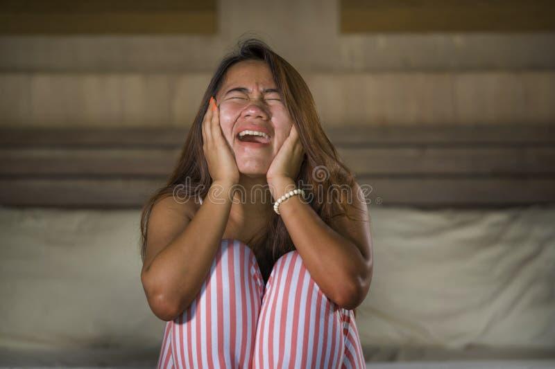Dramatisch levensstijlportret van jonge droevige en gedeprimeerde Aziatische Indonesische vrouw die in pyjama's op bed zitten die stock foto