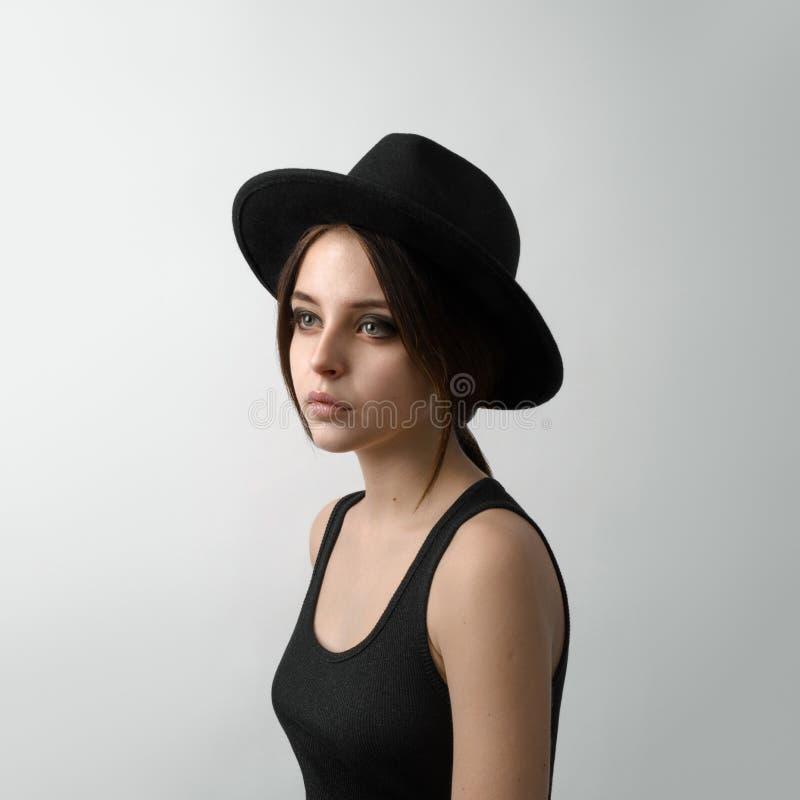 Dramatisch portret van een meisjesthema: portret van een mooi jong meisje in een zwarte hoed en een zwart overhemd op grijze acht stock afbeeldingen
