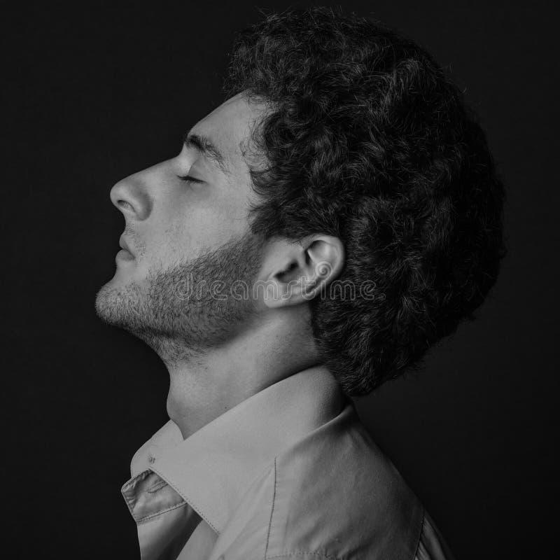 Dramatisch portret van een mensenthema: mensenzitting in profiel die een overhemd met gesloten ogen op een donkere achtergrond in royalty-vrije stock afbeeldingen