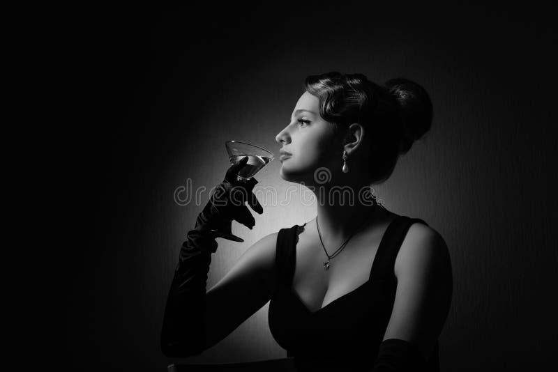 Dramatisch portret van een mooie vrouw met glas van martini stock foto