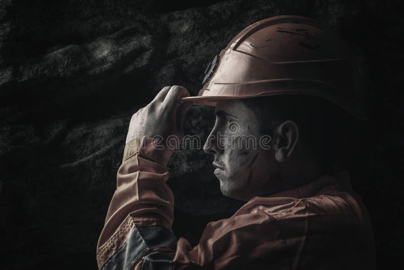 Dramatisch portret van vermoeide spoorarbeider die zijn veiligheid helme houden stock fotografie