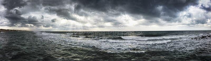 Dramatisch weerpanorama over het overzees die golven bedreigen die bij de kust met donkere hemel en zonnestralen op het water ver royalty-vrije stock afbeeldingen