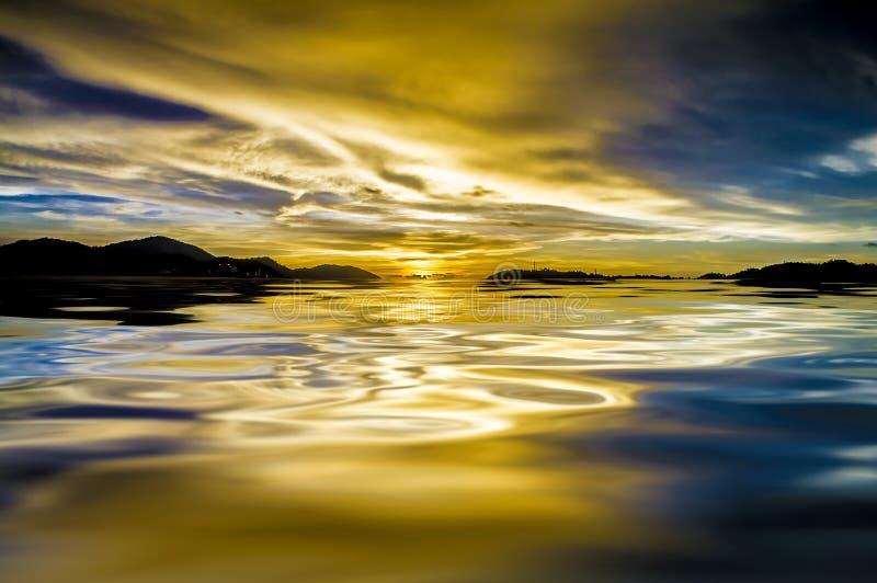 Dramatische hemel en zonsondergangbezinning over water stock foto
