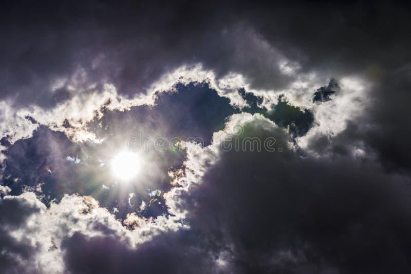 Dramatische hemel met de zon die onder de wolken richten stock afbeelding