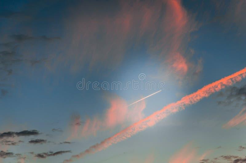 Dramatische hemel met roze strepen Vliegtuig dat in de hemel vliegt royalty-vrije stock foto's
