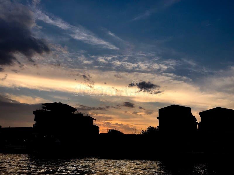 Dramatische hemel met van de de silhouetbouw en rivier mening stock foto