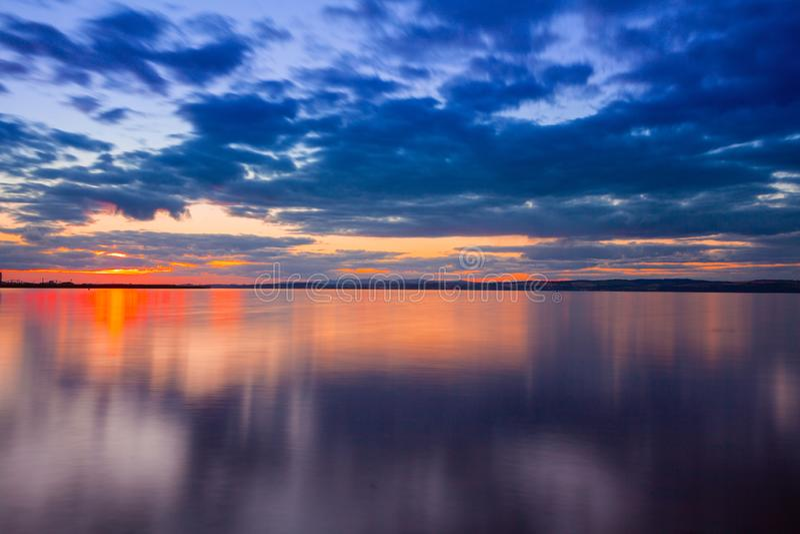 Dramatische kleurrijke trillende die zonsonderganghemel met wolken in het water worden weerspiegeld royalty-vrije stock foto's
