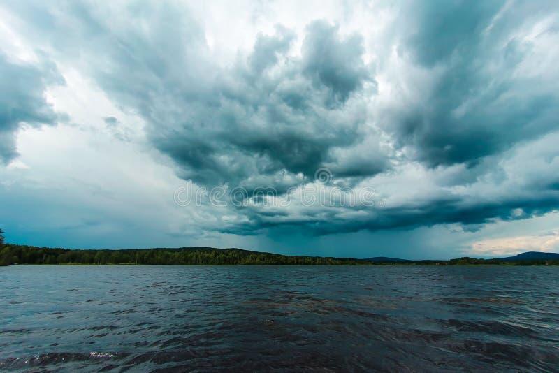 Dramatische lucht boven een meer vlakbij Soderhamn en Hudiksvall in Zweden Donkerblauwe stormachtige wolken, gereflecteerd in don royalty-vrije stock afbeeldingen