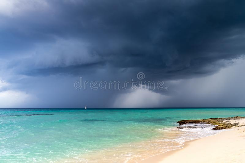 Dramatische mening van donkere grijze onweerswolken tegen het turkooise blauwe water van het Caraïbische overzees en een wit zand royalty-vrije stock foto