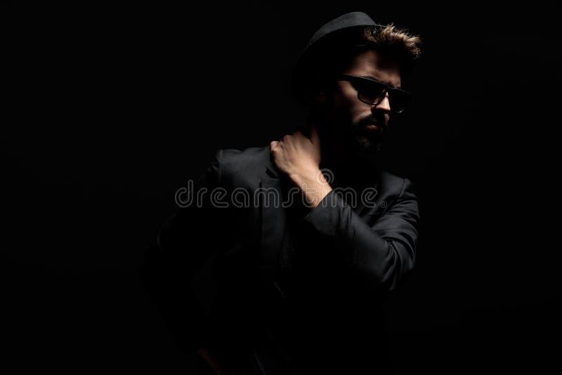 Dramatische mens die en zijn hand op zijn schouder stappen houden stock afbeeldingen