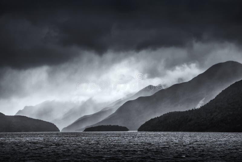 Dramatische onweerswolken meer dan achteruitgaande lagen bergen over Twijfelachtig Geluid in Nieuw Zeeland in zwart-wit stock afbeeldingen