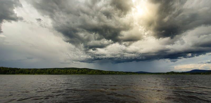 Dramatische regenachtige lucht boven een meer vlakbij Soderhamn en Hudiksvall in Zweden Donkerblauwe ooiewolken en de zon die doo royalty-vrije stock foto's