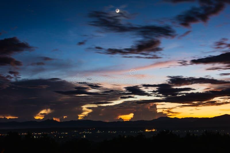Dramatische schemeringhemel met maan boven het licht van kleine stad royalty-vrije stock foto