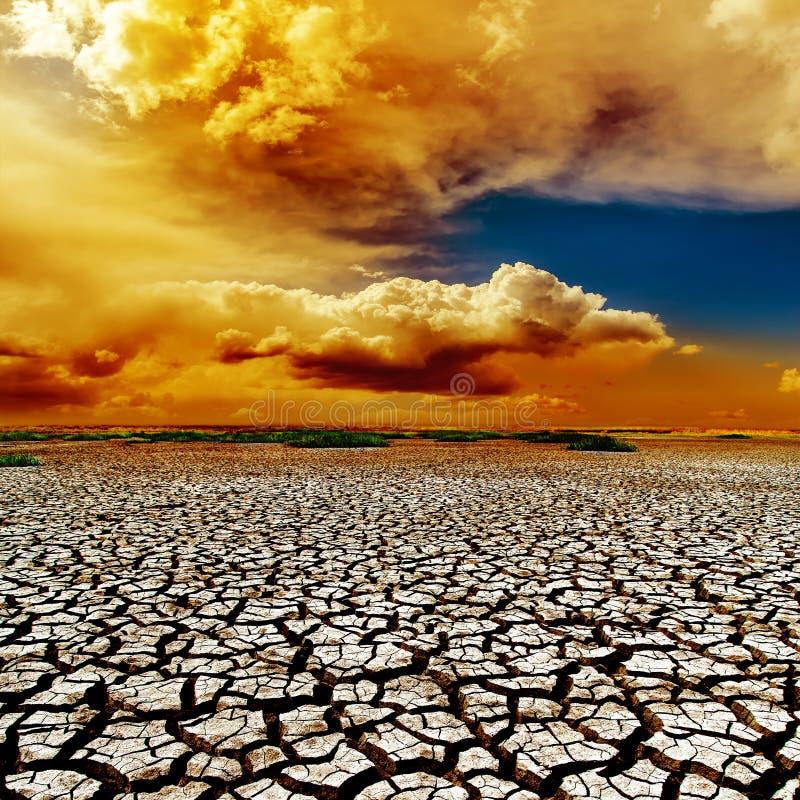 Dramatische wolken over droogteaarde stock foto
