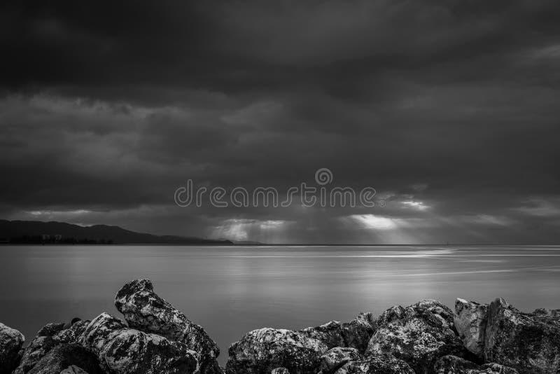 Dramatische zonnestraal door de zware stormachtige wolken van de orkaanregen voorbij de kustlijnbergen stock fotografie