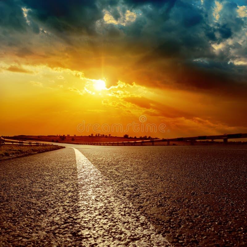 Dramatische zonsondergang en witte lijn op asfaltweg royalty-vrije stock foto