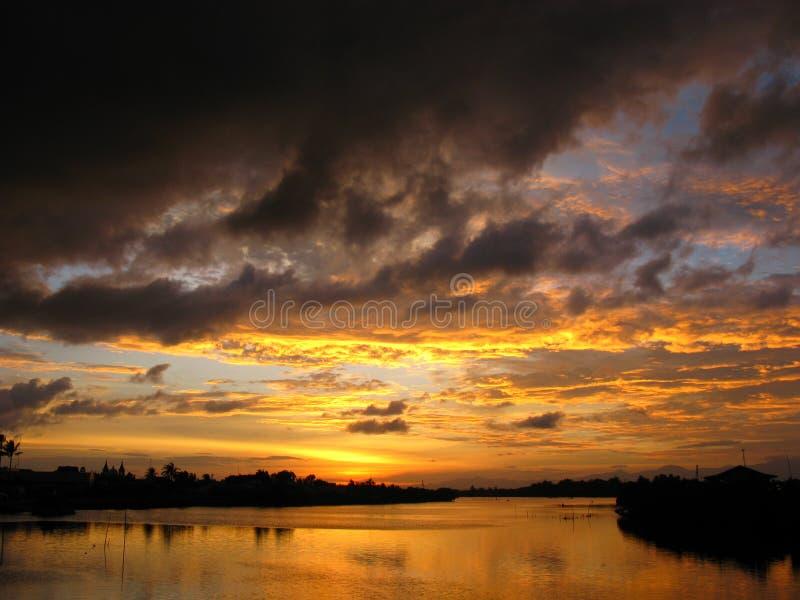 Dramatische Zonsondergang en Wolken over Rivier stock foto's