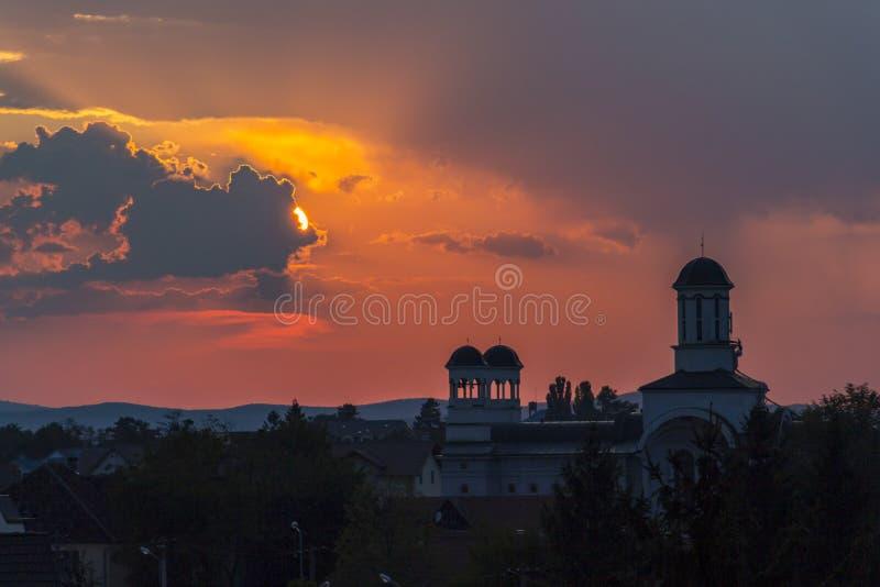 Dramatische zonsondergang over een kerk in Sibiu, Roemeni? stock afbeeldingen