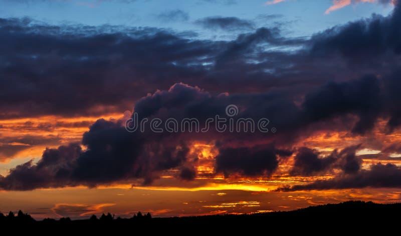 Dramatische zonsonderganghemel met pluizige wolken en vlammende lichten stock foto's