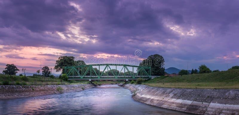 Dramatische zonsonderganghemel over oude metaalspoorwegbrug en vage motierivier royalty-vrije stock foto's