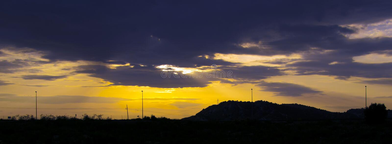 Dramatische Zonsonderganghemel van Trillende Oranje, Gele en Purpere Hemelkleuren met Silhouetten van Lantaarns stock foto's