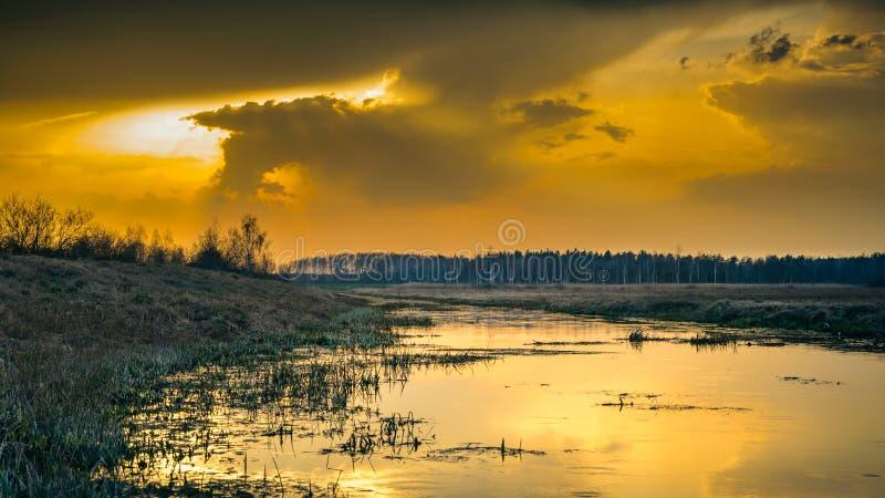 Dramatischer orangefarbener Sonnenuntergang im Herbst auf der Wasseroberfläche in einem schmalen Fluss mit marschfarbenen Grasbän lizenzfreies stockfoto